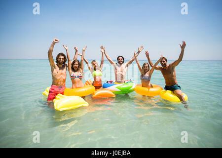 Portrait of cheerful friends enjoying sur joints toriques et la piscine gonflable en radeaux sea against sky Banque D'Images