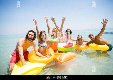 Portrait of cheerful friends enjoying sur anneaux gonflables piscine et mer en radeaux Banque D'Images