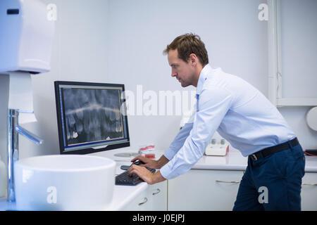 Dentiste attentif examen d'une x-ray sur ordinateur dans une clinique dentaire Banque D'Images