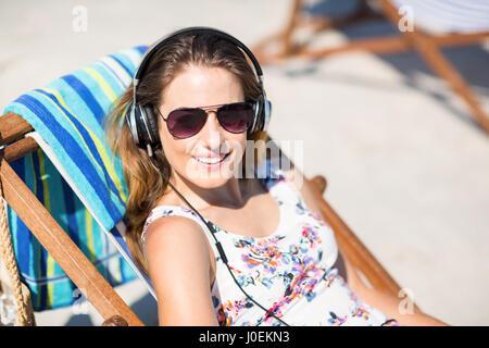 Jeune femme à l'écoute des chansons tout en vous relaxant sur une chaise longue à beach Banque D'Images