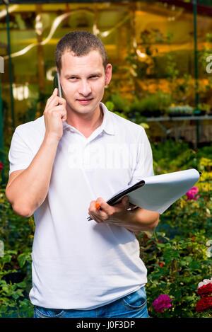 Portrait d'un homme avec un téléphone dans une serre