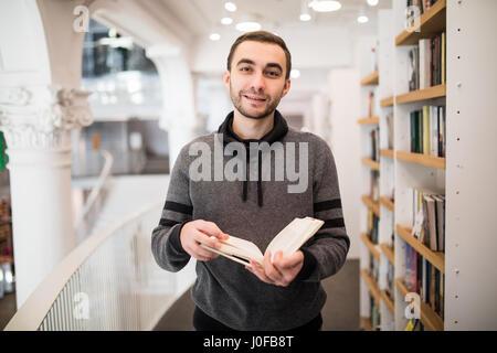 Young caucasian man avec lunettes dans une librairie avec un livre ouvert dans ses mains lire quelque chose avec Banque D'Images