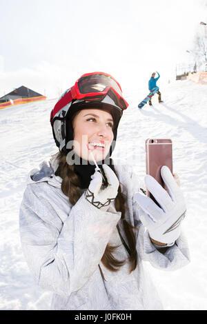 Smiling young female snowboarder appliquant un brillant à lèvres tout en holding smartphone Banque D'Images