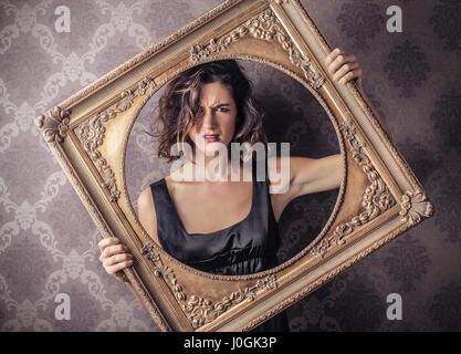 Brunette woman holding a frame Banque D'Images