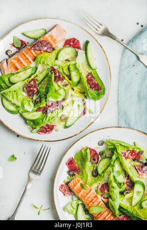 Salade saine avec du saumon grillé, orange, olives, concombre et le quinoa Banque D'Images