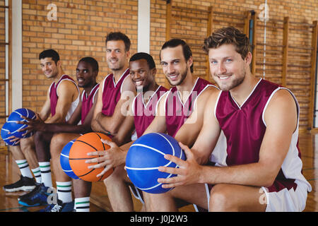 Portrait of smiling de joueurs de basket-ball assis sur un banc avec le basket-ball dans la cour Banque D'Images