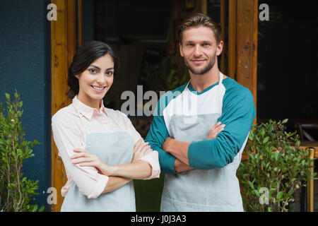 Portrait of smiling waiter et waitress standing with arms crossed en dehors de la cafe Banque D'Images