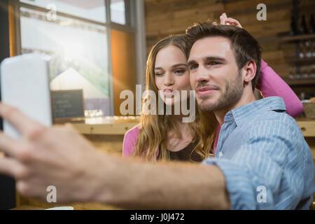 Couple sur téléphone mobile en selfies café Banque D'Images
