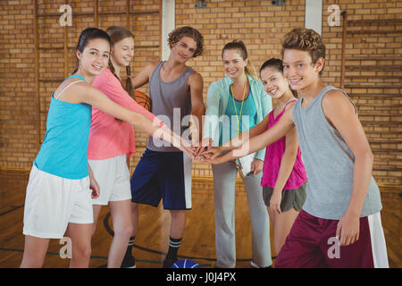 Entraîneuse et lycéens avec leurs mains empilées dans de basket-ball Banque D'Images