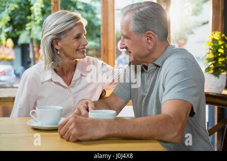 Couple en interaction les uns avec les autres en café Banque D'Images