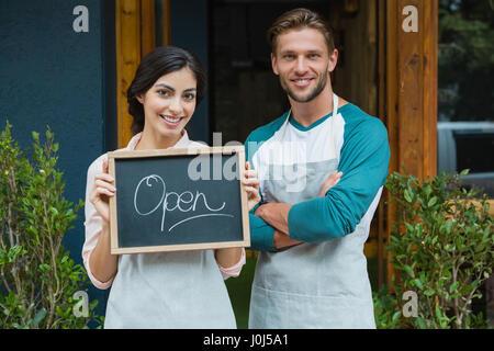 Portrait of smiling waiter et serveuse debout avec tableau à l'extérieur de la cafe Banque D'Images