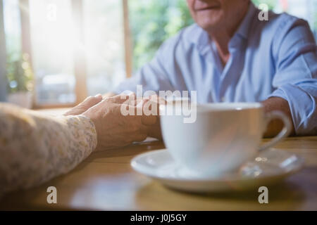 Senior couple holding hands while having coffee in café Banque D'Images