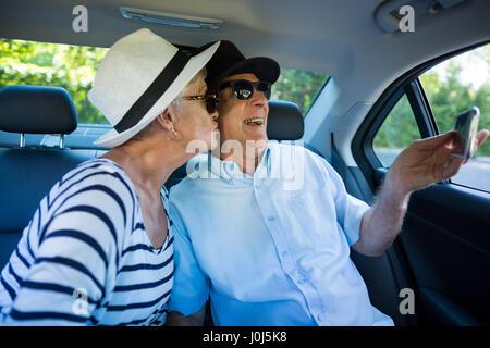 Man tout en l'embrassant femme selfies dans... Banque D'Images