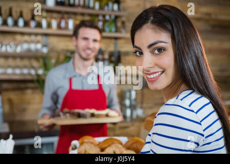 Portrait of smiling woman with waiter standing in background en café Banque D'Images