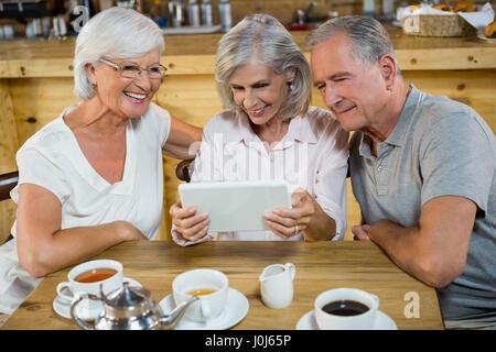 Groupe d'amis using digital tablet in café Banque D'Images