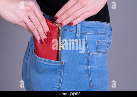 Femme tenant un sac à main rouge qu'elle met dans sa poche Banque D'Images