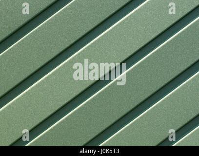 Clôture métallique verdure faite de tôle d'acier ondulée avec des guides verticaux. Fond d'fer vert ondulé close Banque D'Images