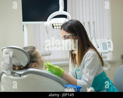 Femme Dentiste Contrôle de petite fille malade Banque D'Images