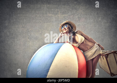 Woman in bikini leaning on beach ball Banque D'Images