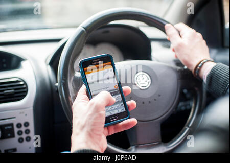 L'homme à l'aide de sms téléphone mobile pendant la conduite Banque D'Images