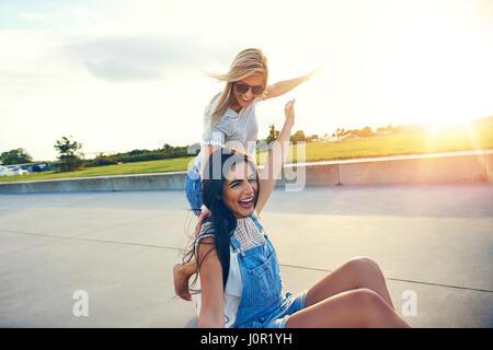 Femme heureuse et ami courir et jouer dehors sur le béton pendant l'été avec un soleil éclatant à l'horizon Banque D'Images