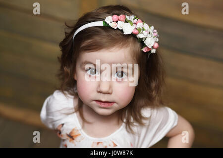 Petite fille aux cheveux bouclés, s'amuser tout en se posant Banque D'Images