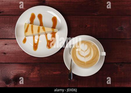 Une tasse de Cappuccino et un morceau de gâteau au fromage, arrosé de sauce au caramel sont en blanc plat sur table Banque D'Images