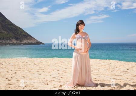 Pregnant woman sitting on beach, berçant son ventre Banque D'Images