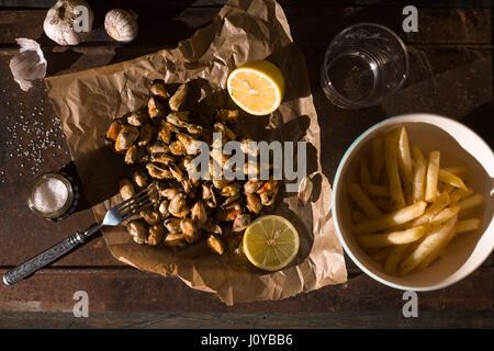 Les moules avec les citrons et les frites sur le fond métallique vue supérieure