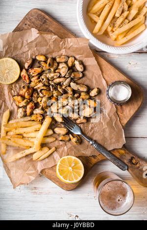 Les moules avec les citrons et les frites sur la table verticale en bois blanc