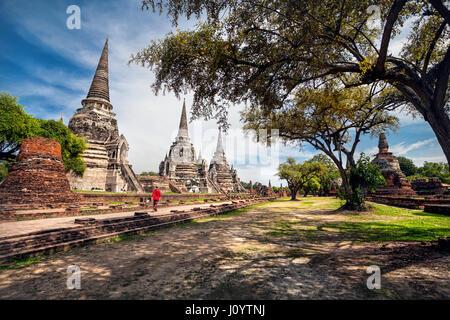 Femme en costume rouge touristiques autour de ruines antiques stupa dans le parc historique d'Ayutthaya, Thaïlande Banque D'Images