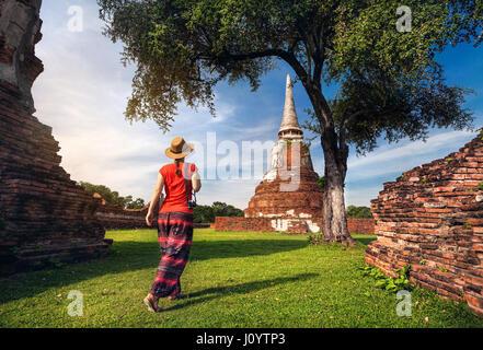 Femme en costume rouge touristiques autour de ruines antiques stupa avec appareil photo dans le parc historique Banque D'Images