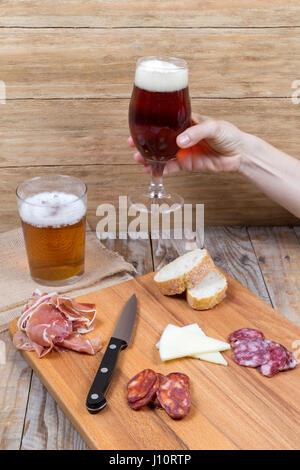 Femme avec un verre de bière et une planche en bois avec un chorizo, jambon et fromage sur une vieille table en Banque D'Images