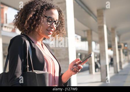 Jeune femme noire attendant le train sur le quai de la gare Banque D'Images