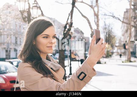 Jeune femme brune dans un manteau beige prend des photos d'elle-même sur un téléphone intelligent dans la ville Banque D'Images