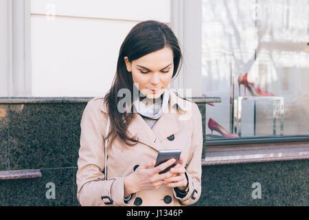 Jeune femme brune en robe beige est titulaire d'un téléphone portable en mains à l'extérieur, close-up Banque D'Images