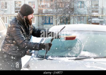 Nettoie l'homme de la neige sur la voiture de verre Banque D'Images