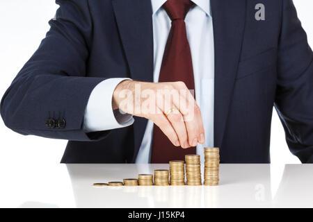 Un homme d'empilage à la main des pièces en euros dans l'augmentation de colonnes. Concept financier. Libre. Banque D'Images