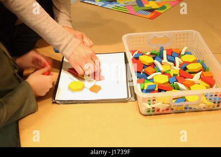 Petit enfant et adultes travaillant sur un puzzle de formes géométriques Banque D'Images