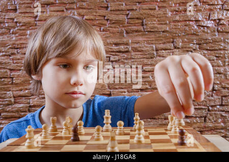 Portrait d'un petit garçon de race blanche en jouant aux échecs et en mouvement suivant