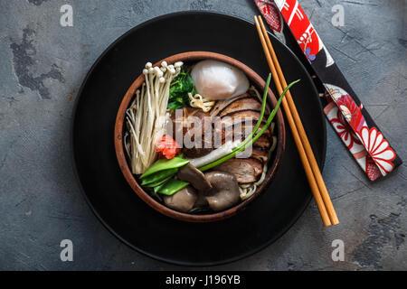 Nouilles Ramen avec du canard, oeuf, champignons shiitake et enoki bouillon avec sur fond sombre Banque D'Images