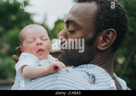 Père avec bébé fils dans ses bras Banque D'Images