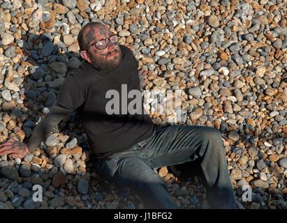 Un homme tatoué de soleil sur la plage de Brighton Banque D'Images