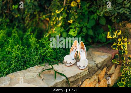 Chaussures de mariage sur une frontière de pierre sur un fond de feuilles vertes Banque D'Images