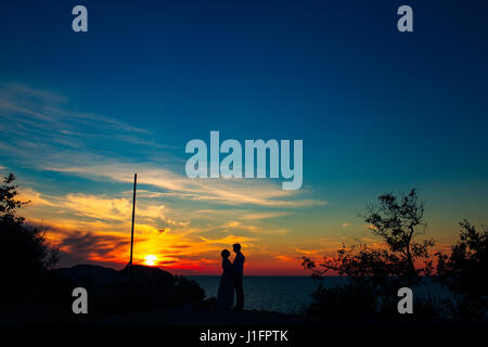 Silhouette d'un couple sur l'arrière-plan du soleil couchant Banque D'Images
