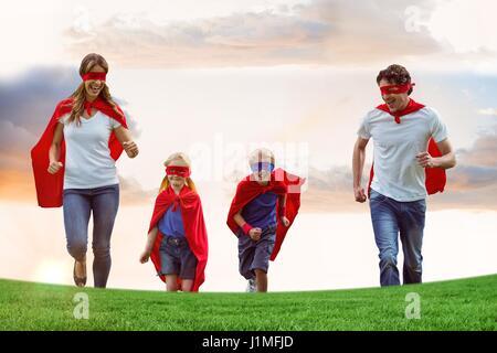 La famille de porter des capes et masques des yeux lors de l'exécution sur terrain against sky Banque D'Images