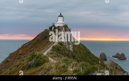 Le lever du soleil, au phare, le Nugget Point, Catlins, Région de l'Otago Southland, Nouvelle-Zélande Banque D'Images