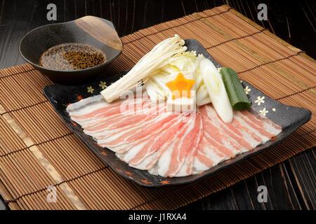 Fillet de porc fraîche sur noir plat avec de la sauce aux champignons, l'oignon et