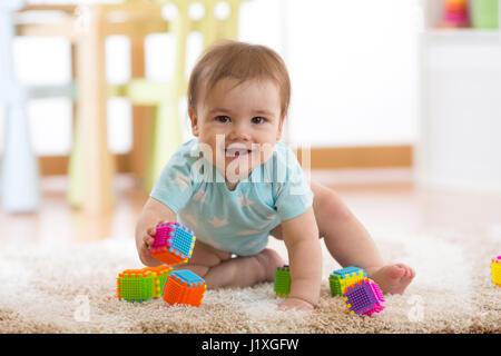 Bébé garçon drôle de ramper sur le plancher à la maison Banque D'Images