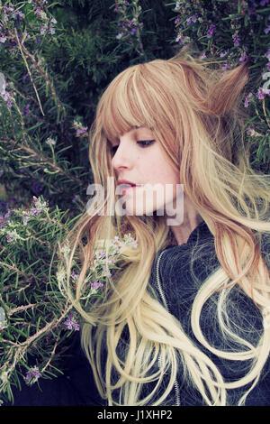 Jeune femme couchée dans un buisson de romarin Banque D'Images